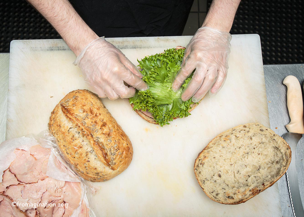 Putting lettuce on a Fromagination Signature Sandwich