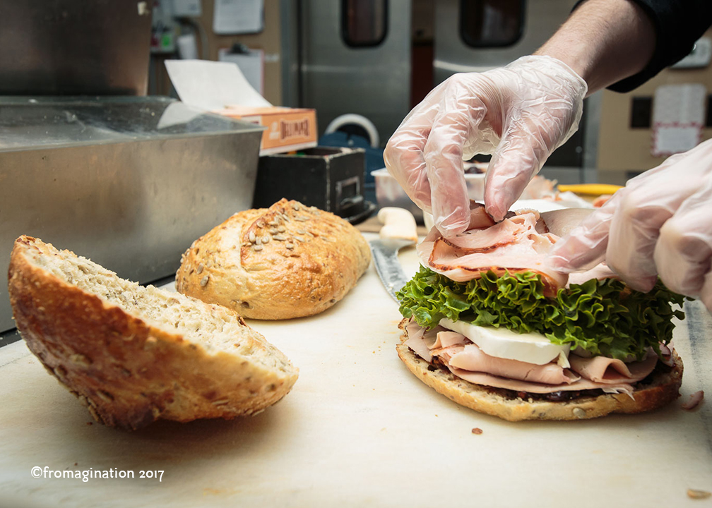 Adding more turkey to a Fromagination Signature Sandwich