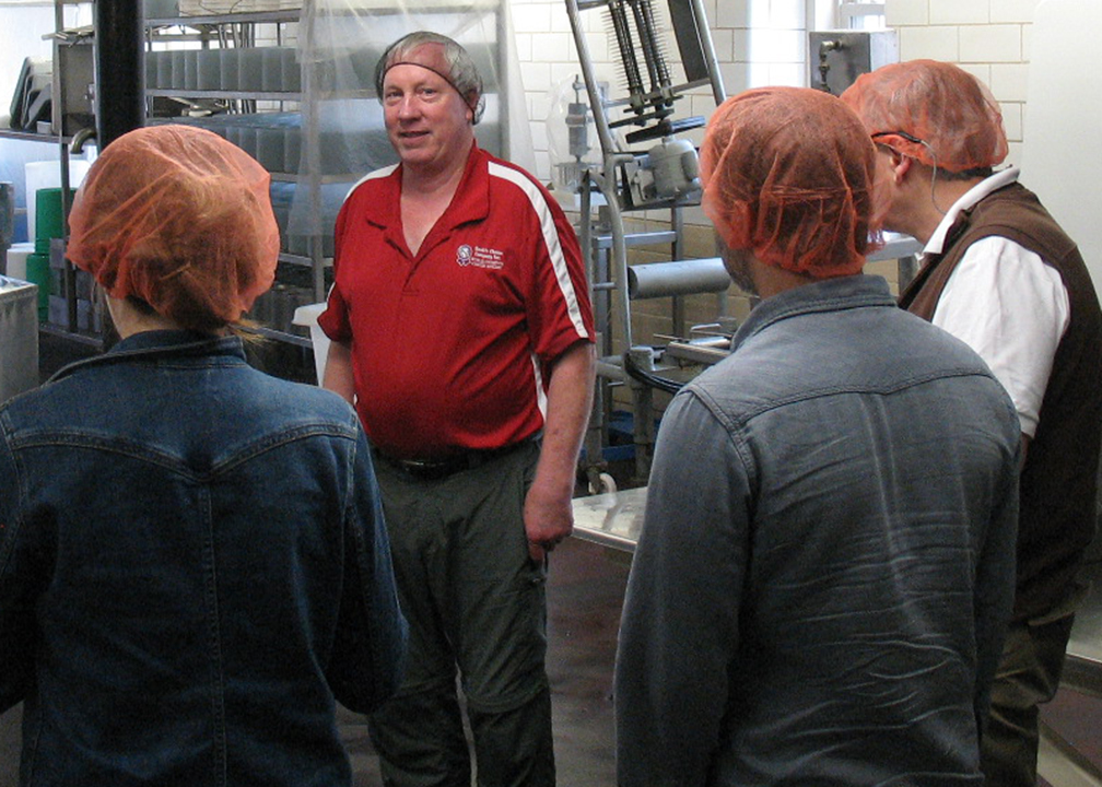 Fromagination employees listen to Tony Hook talk about cheese-making