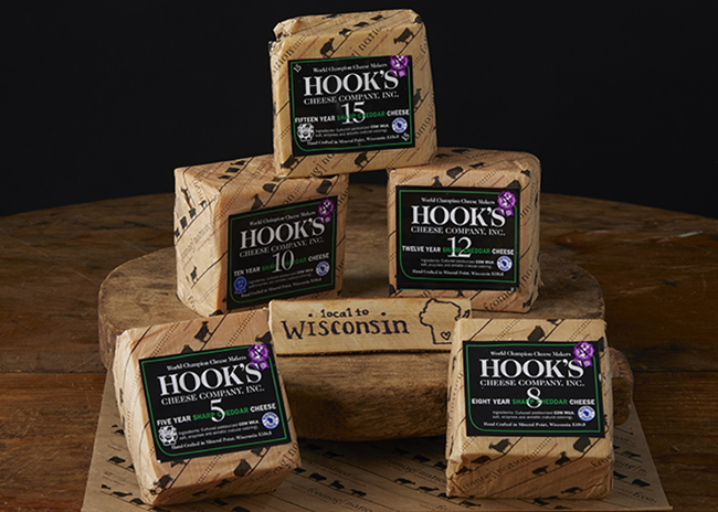 This is a picture of five Hook's aged Cheddar cheeses, offered by Fromagination.