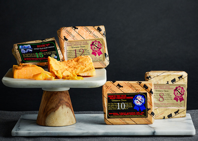This is a picture of four Aged Cheddar cheeses from Hook's Cheese.