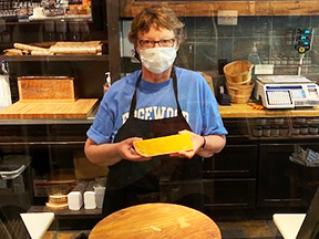 This is a picture of a Fromagination employee masked for COVID-19 in the shop