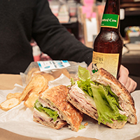 This is a picture of a lunch sandwich and beer from Fromagination